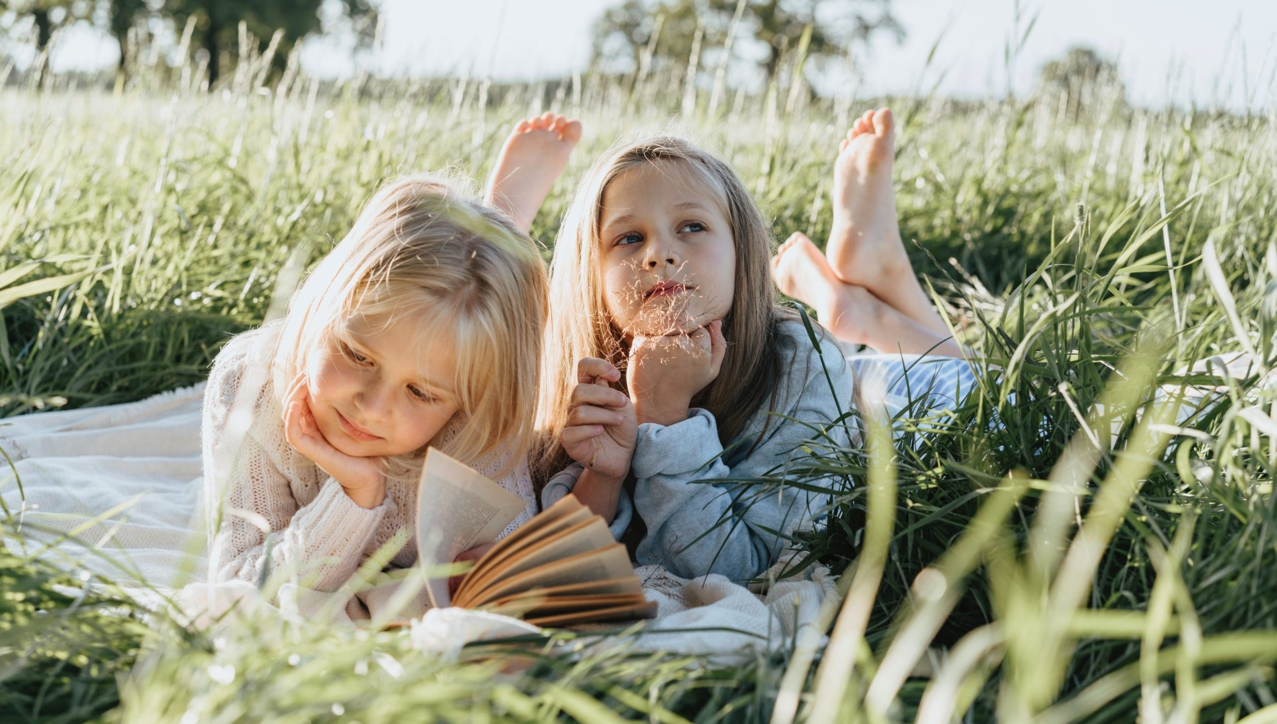two young girls reading a book laying on the grass