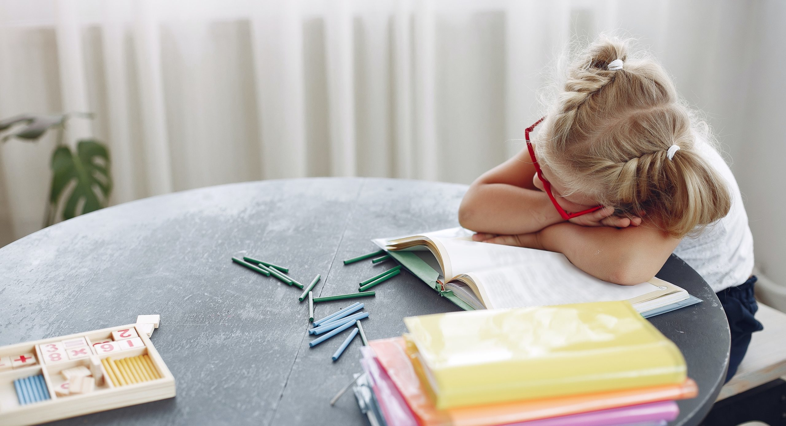 Blonde little girl in red glasses reads a book and seems tired leaning on the table. Fake reading.