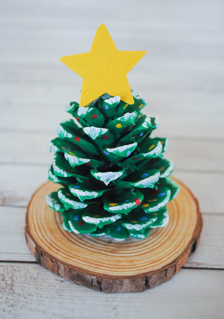 Easy home winter craft with kids. A pine decorated as a mini Christmas tree with a yellow star on top