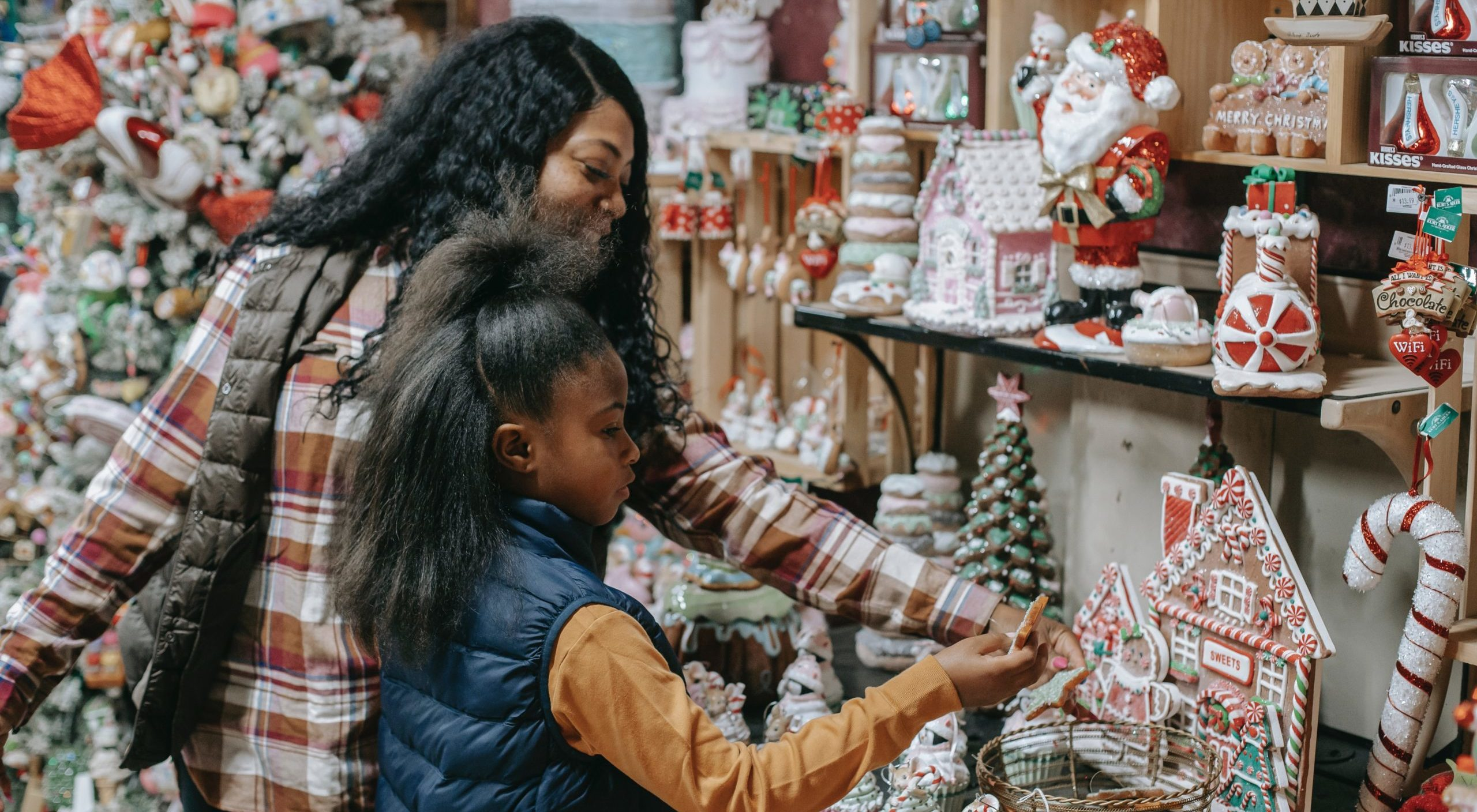 Best winter activities for children. Mother and daughter crossing Christmas decorations and sweets at a Christmas store.